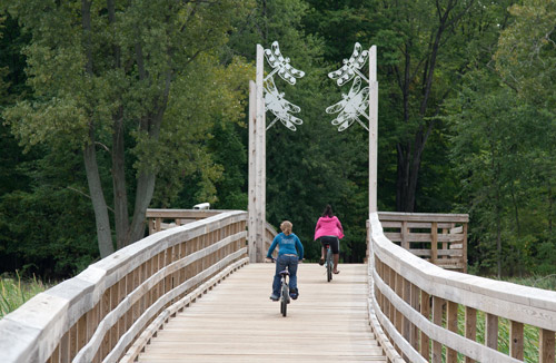 "Photo: Two girls riding the ""dragonfly bridge"" on the Lake-to-Lake Trail. Photo by James Guilford."