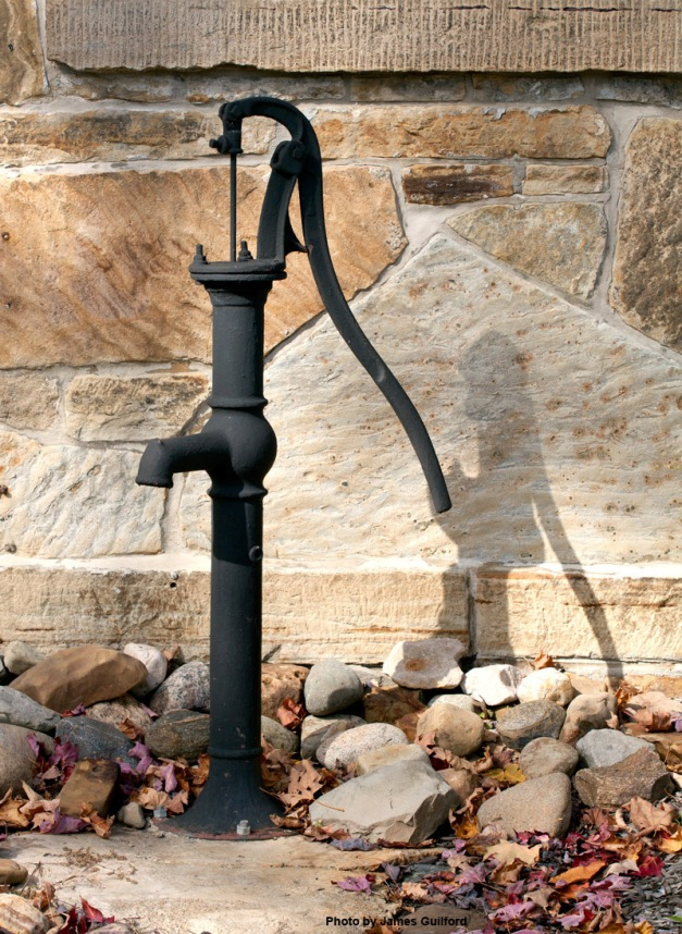 Photo: Water pump near stone wall of an old school. Photo by James Guilford.