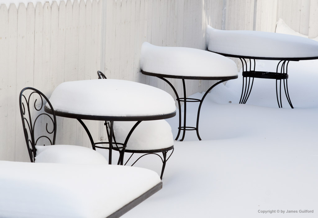 Photo: Snow-covered tables and chairs of a bistro in winter. Photo by James Guilford.