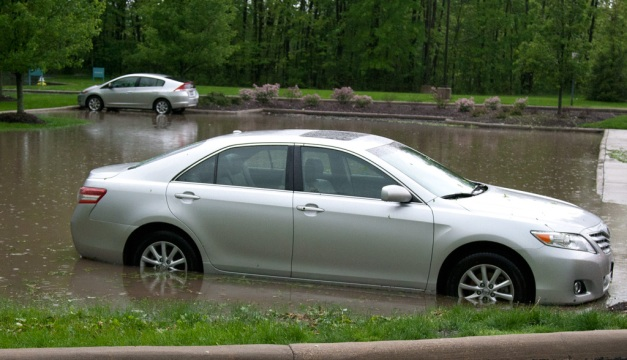Photo: Flooded parking lot maroons two cars. Photo by James Guilford.