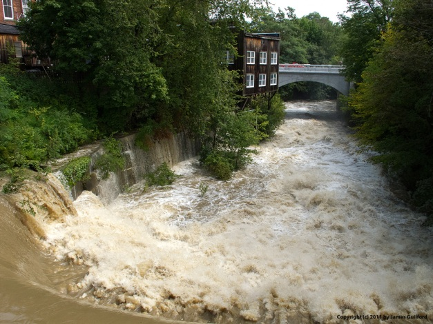 Photo: Brown water raging over a dam following heavy rain. Photo by James Guilford.