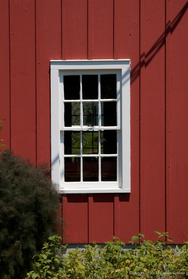 Photo: Deep red barn with white window frame. Photo by James Guilford.