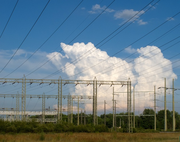 Photo: Cumulus clouds over electrical substation. Photo by James Guilford.