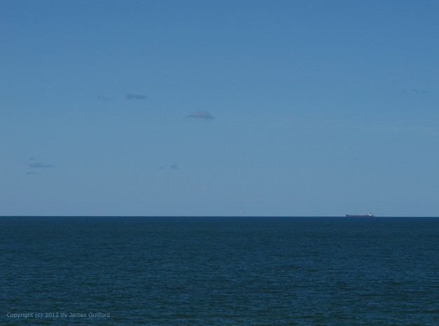 Photo: Lake Erie ore carrier boat on the distant horizon. Photo by James Guilford.