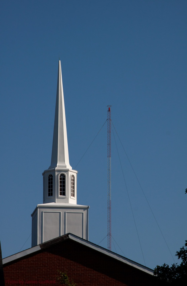 Photo: Church steeple with radio tower in background against a blue sky. Photo by James Guilford.