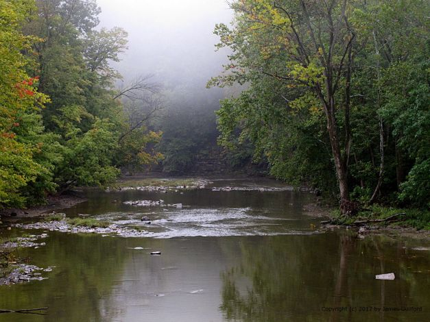 Photo: Still river waters with foggy background. Photo by James Guilford.