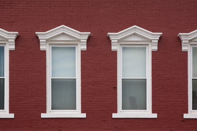 Photo: Red-painted wall with a row of white frame windows. Photo by James Guilford.