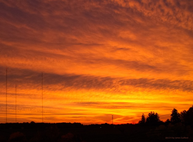 Photo: Glowing sunrise over radio antenna site. Photo by James Guilford.