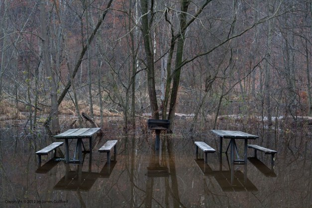 Photo: Picnic tables in a park are reflected in shallow flood waters. Photo by James Guilford.