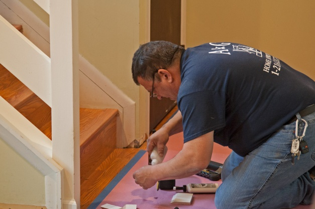 Photo: Workman installing moulding. Photo by James Guilford.