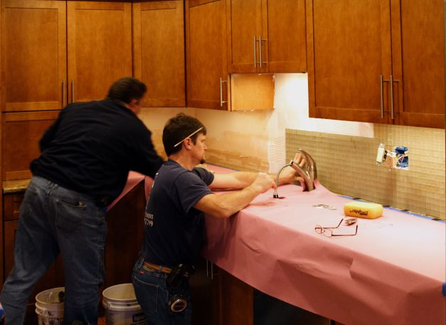 Photo: Two men installing backsplash tile. Photo by James Guilford.