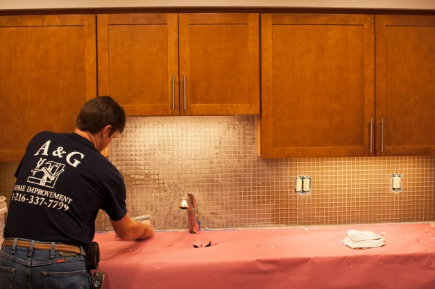 Photo: Worker applies grout to tile. Photo by James Guilford.