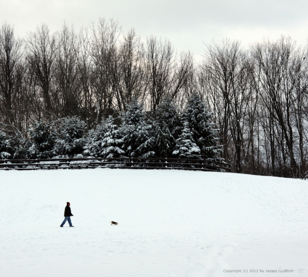 Photo: Man walking his dog in fresh snow. Photo by James Guilford.