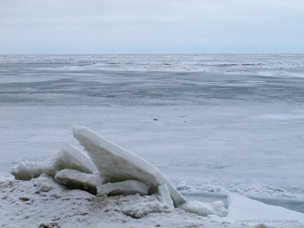 Photo: Fractured ice sheets piled on a beach. Photo by James Guilford.