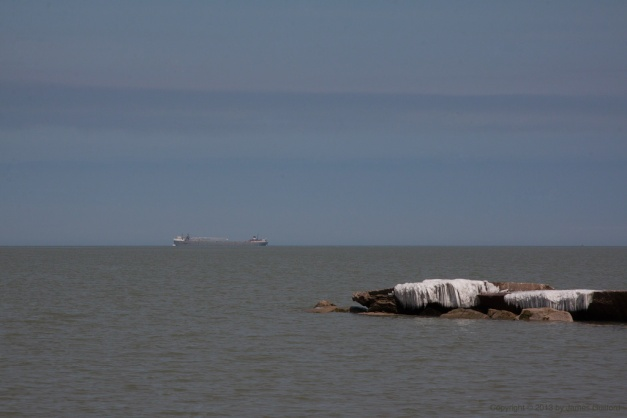 Photo: Lake Erie cargo boat heading west with icy rocks in the foreground. Photo by James Guilford.