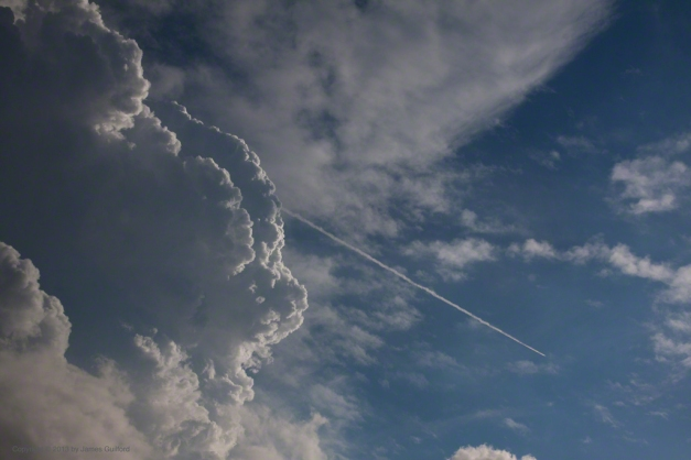 Photo: Aircraft contrail appears ejected from clouds. Photo by James Guilford.