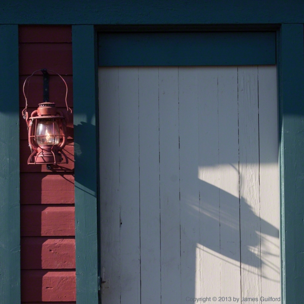 Photo: An antique lantern hangs next to a door. Photo by James Guilford.