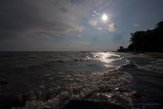 Photo: Waves roll ashore highlighted by beaming sun. Photo by James Guilford.