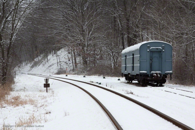 Photo: Lone rail car sits, collecting snow, on a siding. Photo by James Guilford.