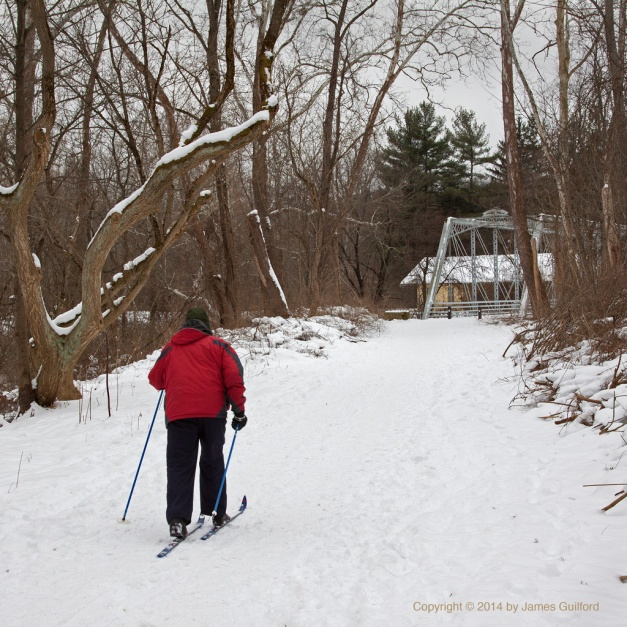 Photo: Cross-country skier on trail to bridge. Photo by James Guilford.