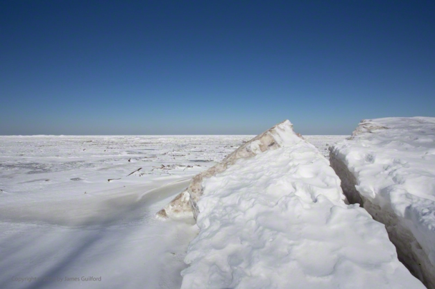 Photo: Piles of broken ice plates rest deep over a Lake Erie beach under a clear winter sky. Photo by James Guilford.