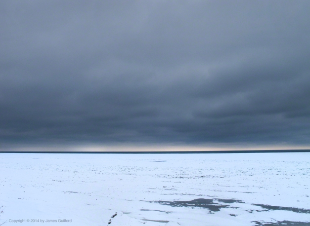 Photo: Glowering clouds over icy Lake Erie. Photo by James Guilford.