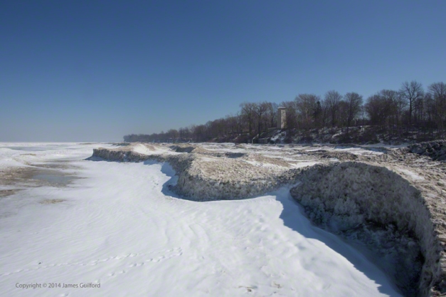 Photo: Sculpted piles of snow and ice form low cliffs along the Lake Erie Shoreline. Photo by James Guilford