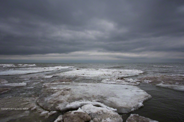 Photo: Dark sky looms over broken plates of ice on Lake Erie. Photo by James Guilford.