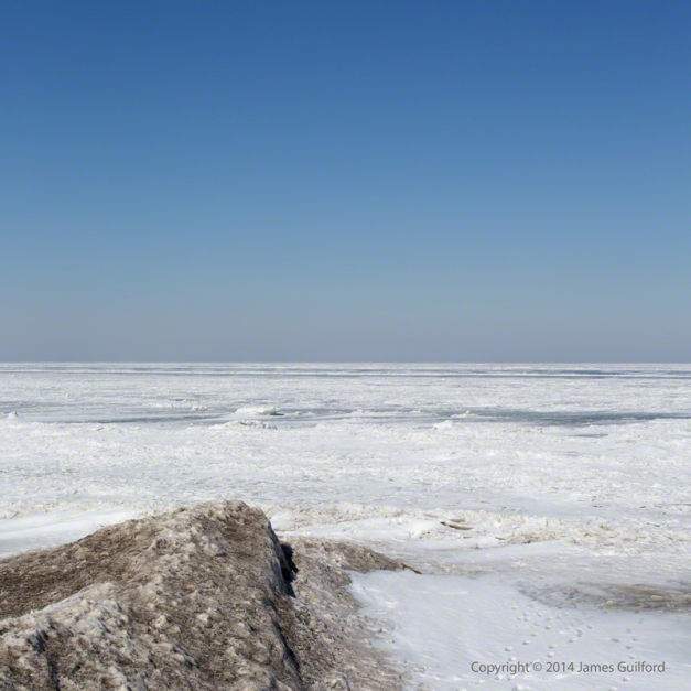Photo: A spit of sand-tinted ice points northward, out on to the barren expanse of Lake Erie in winter. Photo by James Guilford.