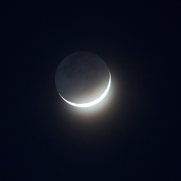 Photo: Crescent Moon through Thin Clouds. Photo by James Guilford.