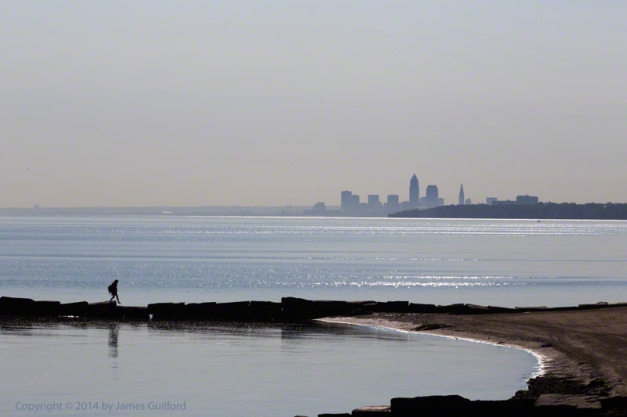 Photo: Woman stepping on stones of breakwall with city in background. Photo by James Guilford.