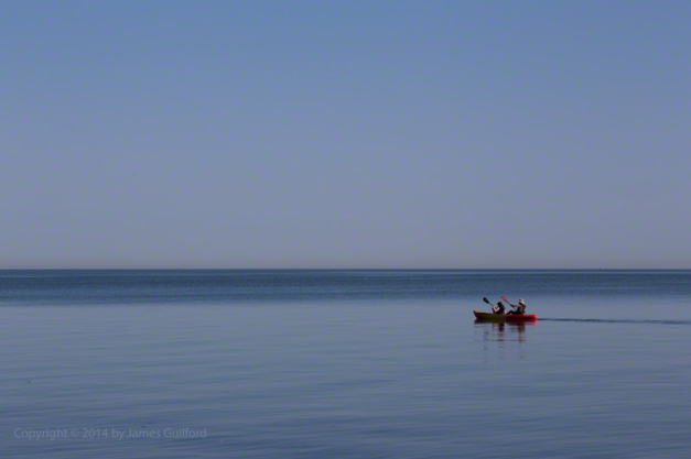 Photo: Kayakers on calm Lake Erie under a blue sky. Photo by James Guilford.