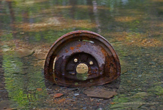 Photo: A rusty automobile wheel sits in a clear running stream. Photo by James Guilford.