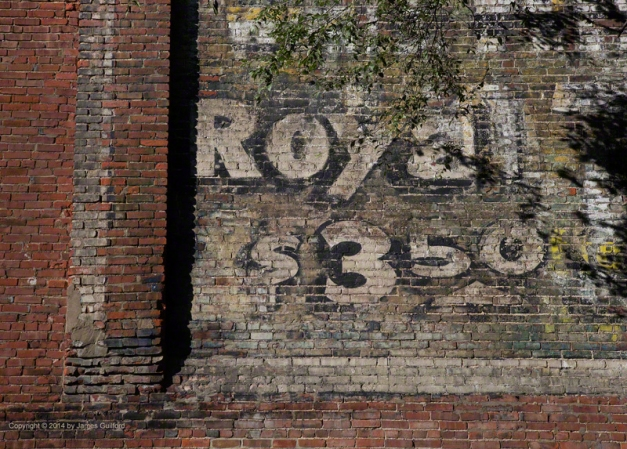 Photo: Faded painted advertising billboard. Photo by James Guilford.