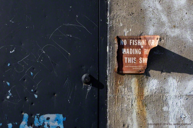 Photo: Damaged door and sign on concrete wall. Photo by James Guilford.