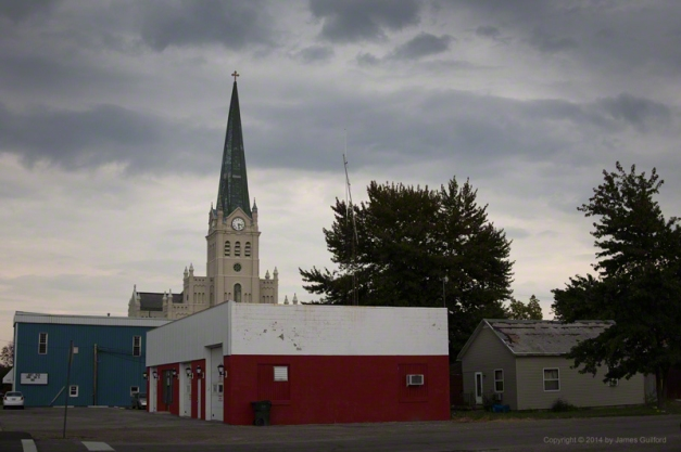 Photo: Beautiful church rises above worn-down buildings under stormy skies. Photo by James Guilford.