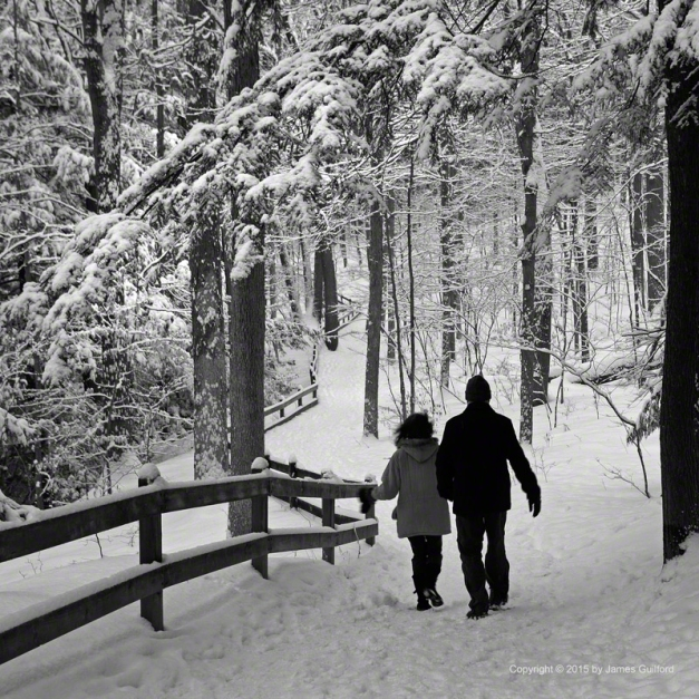 Photo: Couple walking on path in snow-filled landscape. Photo by James Guilford.