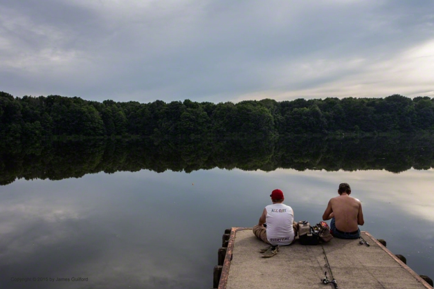 Photo: Father and son fishing on quiet lake in the evening. Photo by James Guilford.