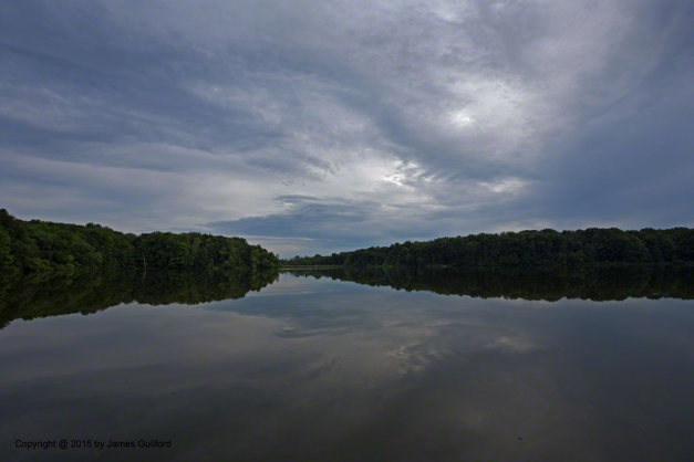 Photo: Late-day clouds reflect in still waters. Photo by James Guilford.