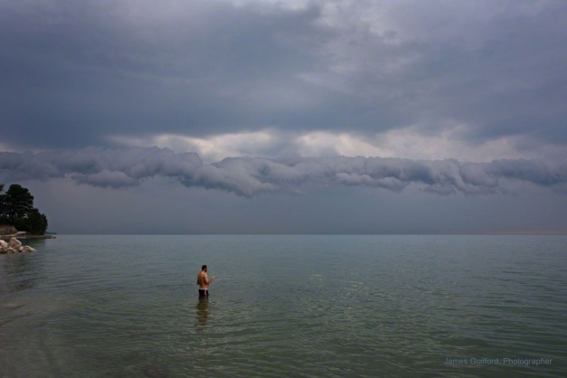 Photo: Man wading in lake as a storm approaches. Photo by James Guilford.