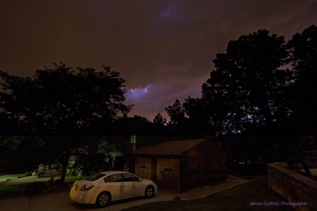 Photo: Nighttime thunderstorm over a house and trees. Photo by James Guilford.