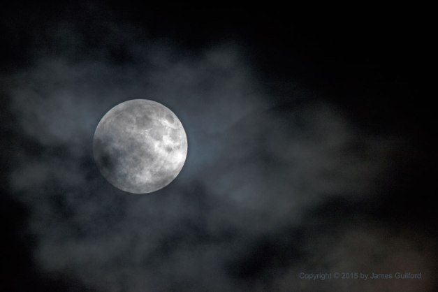 Photo: Pre-eclipse, bright Moon amongst thin clouds. Photo by James Guilford.