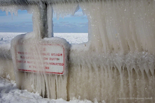 Photo: Guardrail and sign covered in thick curtains of lake water ice. Photo by James Guilford.