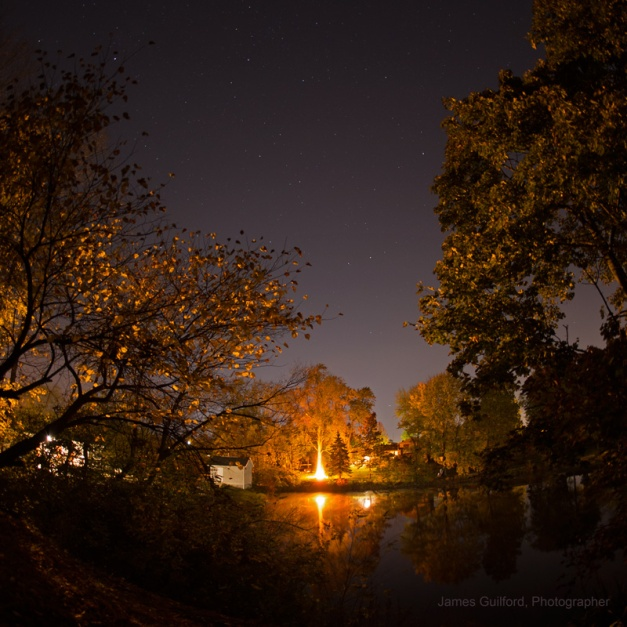 Firetree. Light-polluted night sky, a neighbor's bonfire, and a small pond combine to make a pretty scene with a touch of mystery. You work with what you've got! Photo by James Guilford.