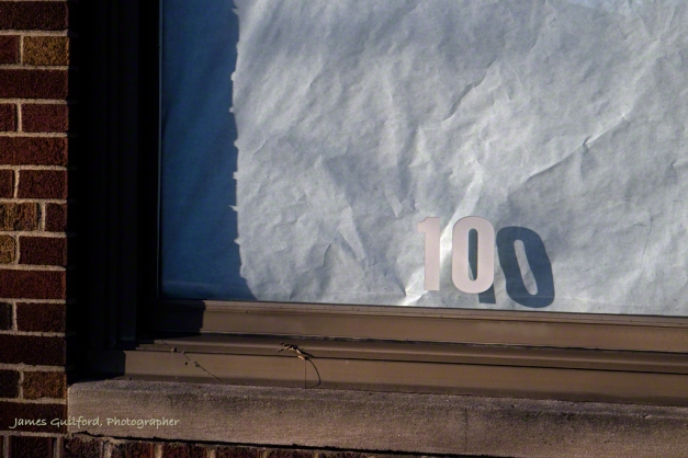 Photo: Letters and shadows in window may read 10 or 100. Photo by James Guilford.