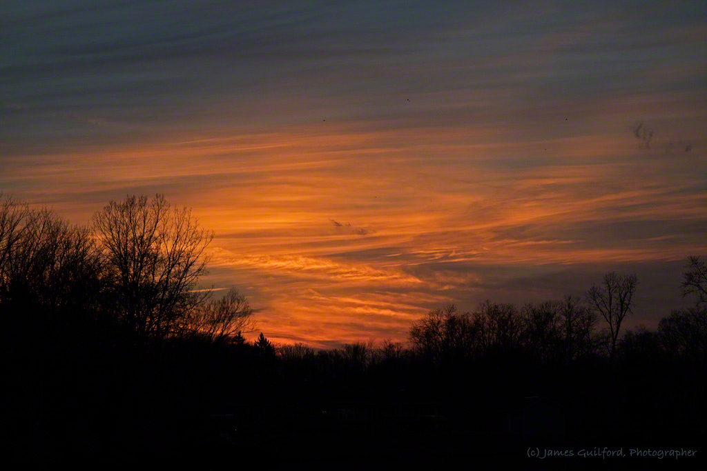 Photo: Cirrus clouds glow orange in sunset rays. Photo by James Guilford.