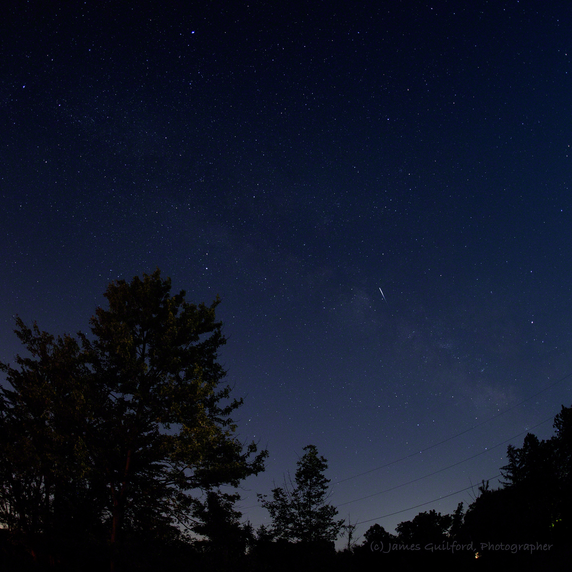 Photo: The streak of a small meteor with the Milky Way as background. Photo by James Guilford.