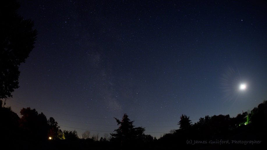 Photo: Wide-angle shot of sky with Milky Way, stars, Moon, and ground visible. Photo by James Guilford.