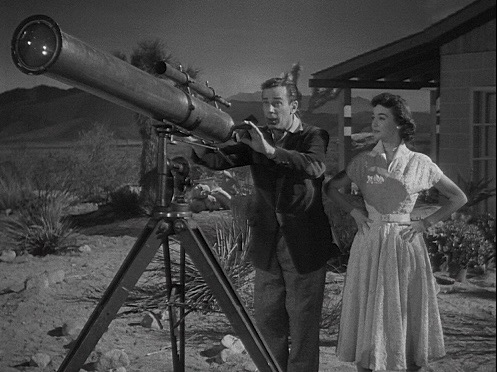 Photo: Man, woman, telescope, movie still. Universal-International