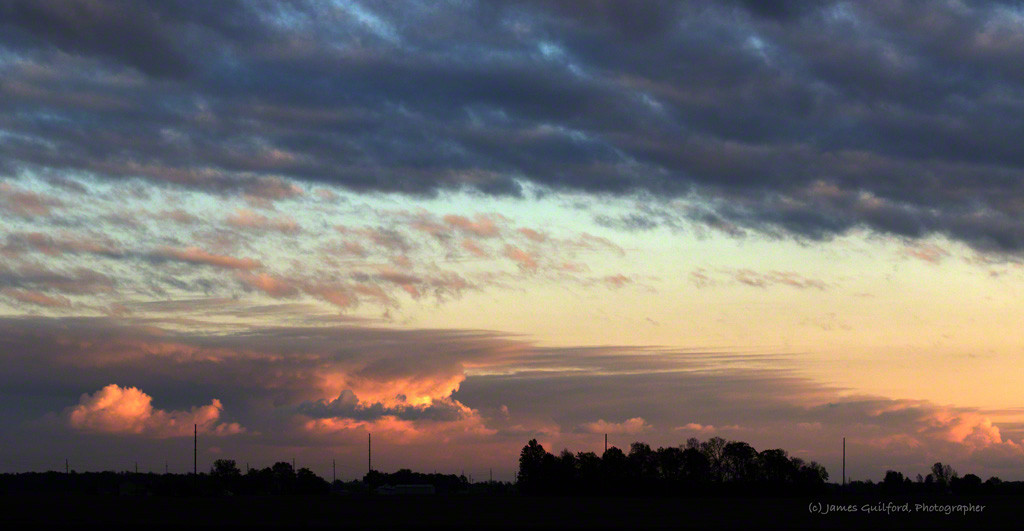 Photo: Sunset-illuminated clouds over rural fields. Photo by James Guilford.